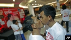Men kiss among other couples participating in the Guinness World Record attempt in the longest continuous kiss in Pattaya, Thailand, February 12, 2012.