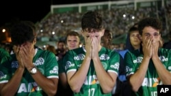 Chapecoense soccer players who did not travel with their team on a flight to Colombia that crashed, mourn during a tribute to the crash victims at Arena Condado stadium in Chapeco, Brazil, Nov. 30, 2016.