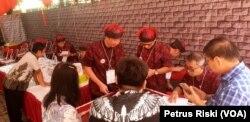 Petugas TPS berpakaian tradisional Tionghoa melayani warga yang hendak memilih (Foto: VOA/Petrus Riski).