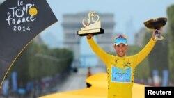 Pebalap sepeda Italia Vincenzo Nibali mengangkat trophy Tour de France dalam upacara di Champs Elysees di Paris Minggu (27/7).