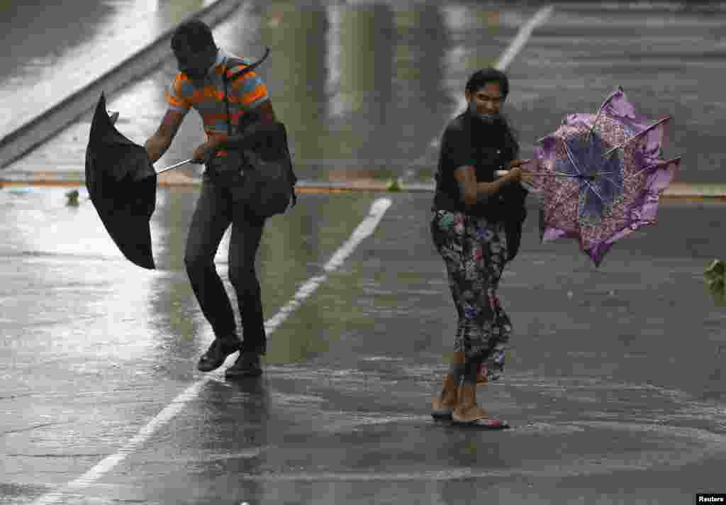 A man and a woman struggle to hold their umbrellas due to high wind and rain in Colombo, Sri Lanka.