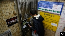 A mainland Chinese tourist checks the door of the closed Causeway Bay Bookstore which is known for gossipy titles about Chinese political scandals and other sensitive issues that are popular with visiting tourists from the mainland, in Hong Kong, Feb. 5, 2016.