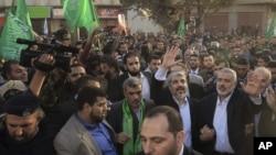Lãnh tụ lưu vong của Hamas, ông Khaled Meshaal (trái), và Thủ tướng của Hamas ở Gaza, ông Ismail Haniyeh, vẫy tay trong lúc đi qua đường phố ở thành phố Gaza, 7/12/2012