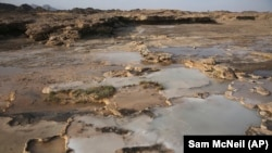 This March 5, 2017 photo shows travertine pools with white films of carbon fused with calcium, a chemical process being explored by a geological research project, in the al-Hajjar mountains of Oman. (AP Photo/Sam McNeil)