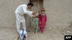 FILE - An Afghan health worker administers polio vaccine to a child during a campaign at a refugee camp on the outskirts of Jalalabad in Nangarhar province, May 11, 2015.