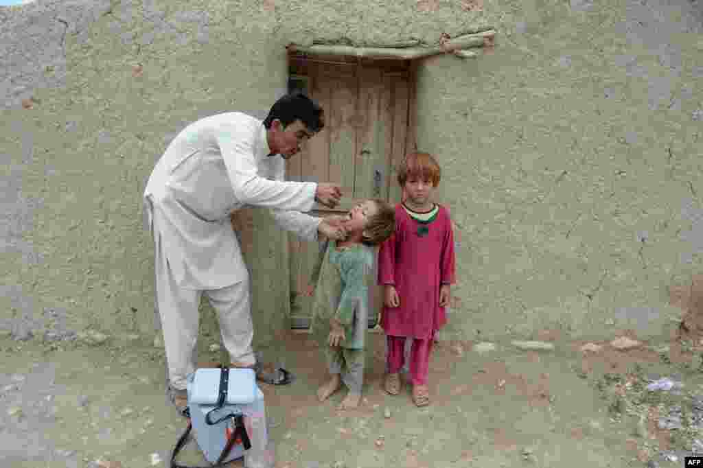 An Afghan health worker gives the polio vaccine to a child during a campaign at a refugee camp on the outskirts of Jalalabad in Nangarhar province. Polio, once worldwide, is in endemic in just three countries now: Afghanistan, Nigeria and Pakistan.
