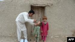 افغانستان میں ایک شخص بچوں کو پولیو کے قطرے پلا رہا ہے۔ (فائل فوٹو)