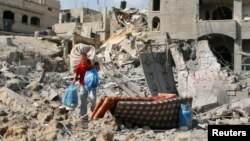 یک مرد فلسطینی در حال حمل وسایل شخصی خود در میان ویرانههای باقی مانده از خانهاش در بین حانون در شمال نوار غزه – ۴ امرداد ۱۳۹۳