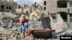 ຊາວປາແລສໄຕນ໌ຄົນນຶ່ງ ຫອບສິ່ງຂອງໆລາວ ຈາກເຮືອນ ທີຖືກທຳລາຍ ຢູ່ເມືອງ Beit Hanoun ຊຶ່ງພວກທີ່ເຫັນ ເຫດການເວົ້າວ່າ ໄດ້ຮັບຄວາມເສຍຫາຍຢ່າງໜັກ ຈາກການຍິງປືນໃຫຍ່ ແລະການໂຈມຕີທາງອາກາດ ຂອງອິສຣາແອລ (26 ກໍລະກົດ 2014)