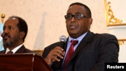 FILE - Somalia's parliament has endorsed the new cabinet of Prime Minister Omar Abdirashid Ali Sharmarke, right. He's shown addressing delegates after being nominated for his post by President Hassan Sheikh Mohamud, left, in Mogadishu, Dec. 17, 2014.