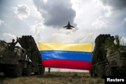 FILE - A Russian-made Sukhoi Su-30MKV fighter jet of the Venezuelan Air Force flies over a Venezuelan flag tied to missile launchers, during the
