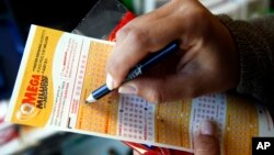 FILE - A customer picks numbers for a Mega Millions lottery ticket at a convenience store in Chicago.