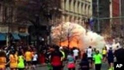 在这张视频截图显示波士顿马拉松赛现场发生两起爆炸,观众和运动员四散躲避