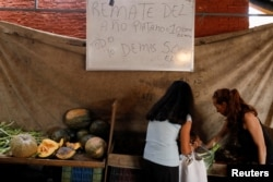 "People shop at a vegetable street market in front of a whiteboard that reads ""Auction of the year. Plantain 10.000 Bolivars per Kg. Everything else 5.000 Bolivars per Kg"", in Caracas, Venezuela, Dec. 19, 2017."