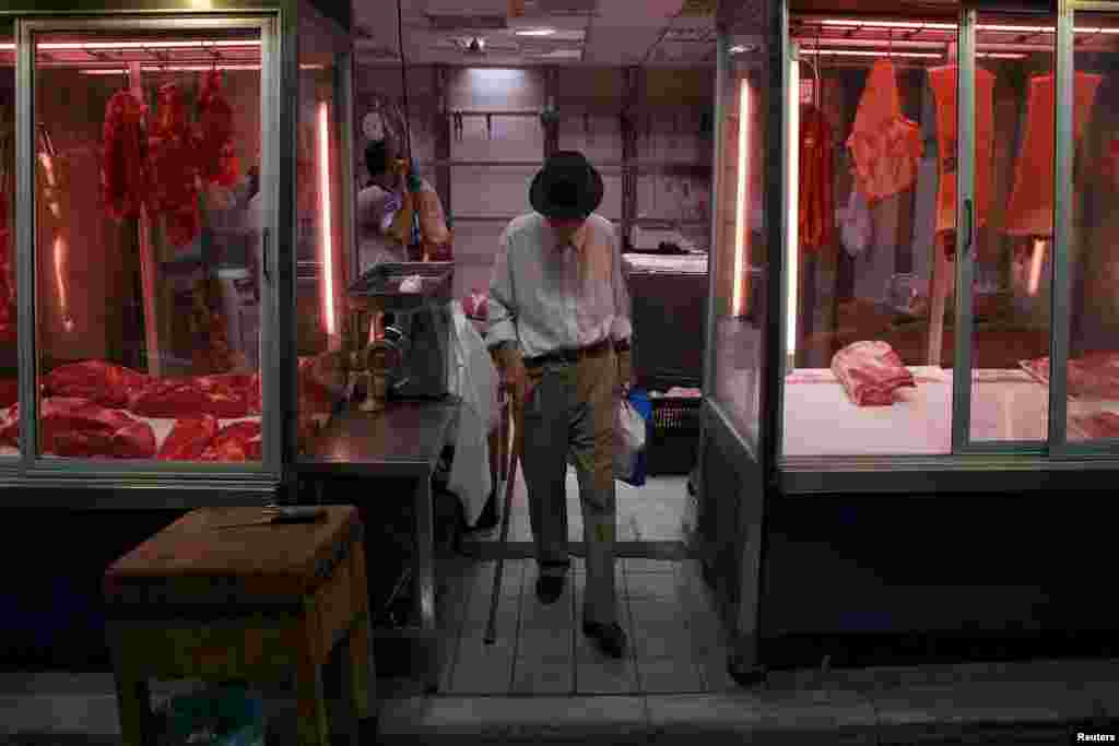 A man exits a butcher shop at the main food market in central Athens, July 20, 2015.