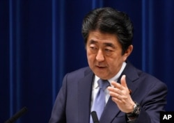 FILE - Japan's Prime Minister Shinzo Abe answers a question from a journalist during a press conference at the prime minister's official residence in Tokyo, July 20, 2018.