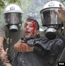 Polisi anti-huru-hara menahan seorang pengunjuk rasa di Lapangan Konstitusi, Athena, Rabu (29/6).