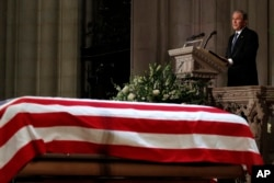 Former President George W. Bush speaks in front of the flag-draped casket of his father, former President George H.W. Bush, at the State Funeral at the National Cathedral, Dec. 5, 2018, in Washington.