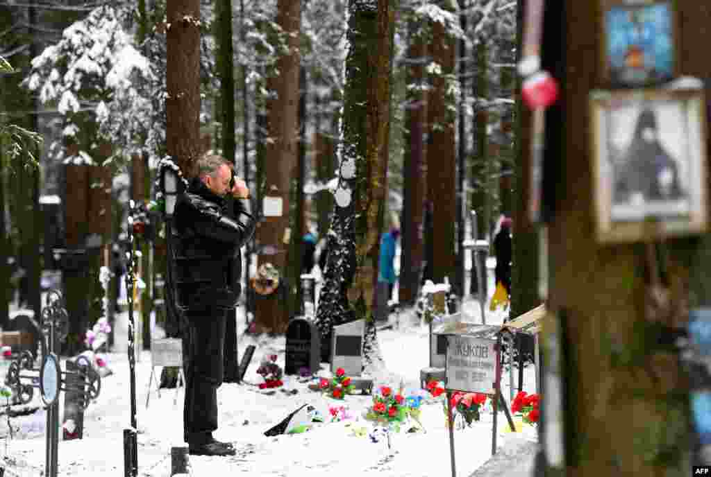 A man crosses himself at the memorial, where the victims of Soviet dictator Joseph Stalin's regime were buried in the woods on the outskirts of Saint Petersburg.