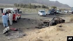 This photo taken by freelance photographer Abdul Malik on Saturday, May 21, 2016, purports to show volunteers standing near the wreckage of the destroyed vehicle, in which Mullah Mohammad Akhtar Mansour was allegedly traveling in the Ahmed Wal area in Baluchistan province of Pakistan, near Afghanistan border. A senior commander of the Afghan Taliban confirmed on Sunday that the extremist group's leader, Mullah Mohammad Akhtar Mansour, has been killed in a U.S. drone strike. (AP Photo/Abdul Malik)