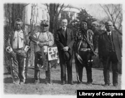 This 1925 photo shows President Calvin Coolidge posed with unidentified Native Americans, near the south lawn of the White House, shortly after passage of the Native American Citizenship Act of June 1924.