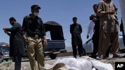 巴基斯坦安全官員星期天站立在奎達為紅十字會工作的英國醫生哈利勒‧戴爾的遺體旁邊