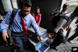 Cảnh sát Malaysia mặc thường phục mang một máy vi tính từ công ty 1MDB ra sau cuộc bố ráp ở Kuala Lumpur, Malaysia, ngày 8/7/2015.