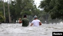 """飓风""""巴里""""过后,路易斯安那州的人们艰难地穿过被洪水淹没的街道。(2019年7月13日)"""