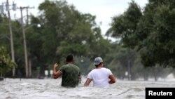 Dos hombres caminan por una calle inundada tras el paso del huracán Barry en Mandeville, Louisiana, EE.UU., el sábado,13 de julio de 2019.