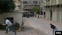 Para demonstran anti-pemerintah di kota Banias melempari polisi Suriah dengan batu (27/5).