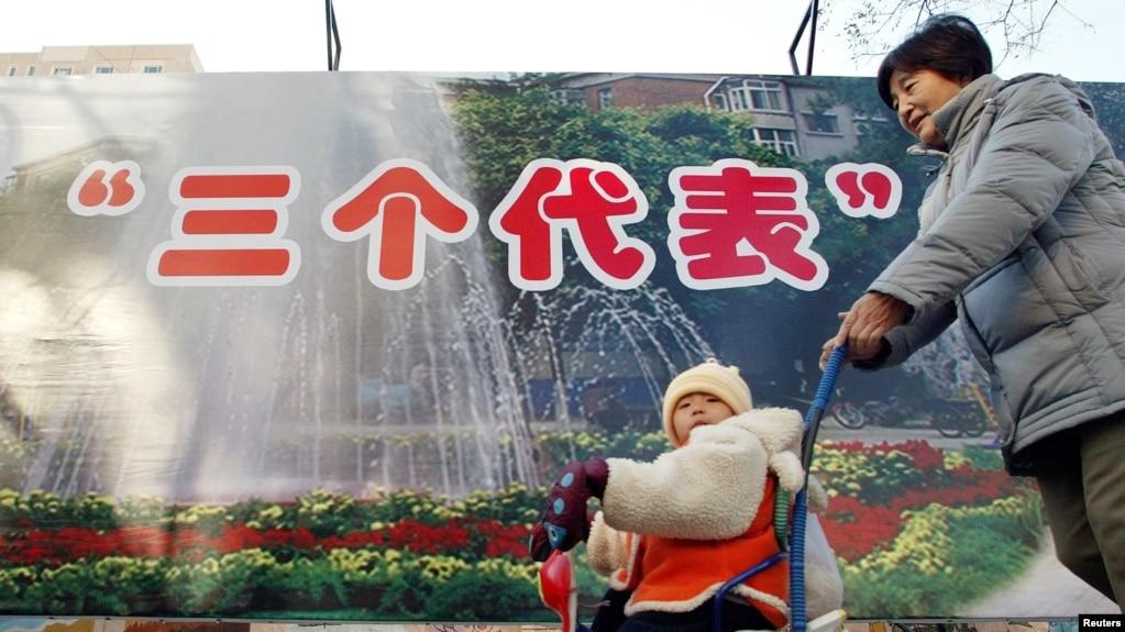 """2002年11月28日,北京的一位母亲推着婴儿走过""""三个代表""""思想的宣传牌。中共说""""三个代表""""思想是江泽民的重要理论贡献。民间把""""三个代表""""思想和""""资本家入党""""联系起来。"""