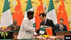 Le président Muhammadu Buhari du Nigeria, à gauche, et son homologue chinois Xi Jinping, à droite, se serrent la main lors d'une cérémonie de signature des accords au Grand Palais du Peuple, à Beijing, Chine, 12 avril 2016. epa/ Kenzaburō FUKUHARA / POOL