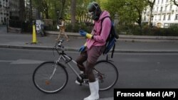 In this April 20, 2020 file photo, a delivery man, who want to name Moise, wearing protective gear checks his phones during a nationwide confinement in Paris. (AP Photo/Francois Mori, File)