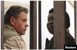 FILE - A combination photo shows Zimbabwean safari operator Honest Ndlovu (R) and fellow countryman and hunter Theo Bronkhorst waiting to appear in Hwange magistrates court, July 29, 2015.