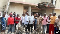 Onlookers gather around a car destroyed in a blast next to St. Theresa Catholic Church in Madalla, Nigeria, Sunday, Dec. 25, 2011. An explosion ripped through a Catholic church during Christmas Mass near Nigeria's capital Sunday, killing scores of people,