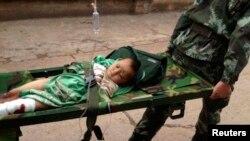 中國雲南省昭通市魯甸龍頭山鎮發生地震後,救援人員用擔架抬走一個受傷的孩子