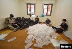 Sukarelawan menyiapkan kantong untuk tempat makanan yang akan dibagikan kepada orang-orang yang membutuhkan selama bulan suci Ramadan, di tengah pandemii COVID-19, di Maan, Yordania 1 Mei 2021. Foto diambil 1 Mei 2021. (REUTERS / Muath Freij)