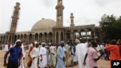 In this photo taken on Aug. 8, 2013, Nigerian Muslims walk past an uncompleted mosque in Maiduguri, Nigeria.