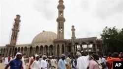 Warga Muslim Nigeria berjalan melewati sebuah masjid di Maiduguri, Nigeria, pada hari raya Idul Fitri.