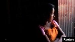 Bé gái mười bốn tuổi hành nghề mại dâm ngồi chờ khách tại một nhà chứa ở Faridpur, ở trung tâm Bangladesh.
