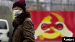 Arhiva - Čovjek nosi masku ispred murala na kome je predstavljena modifikovan amblem vladajuće Komunističke partije Kine, tokom izbijanja epidemije koronavirusa, 28. januara 2020. (REUTERS/Aly Song)