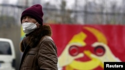 一名戴着口罩的男子走过上海街头一处中共徽标的图案。(2020年1月28日)