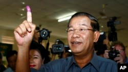 FILE PHOTO - Cambodia's Prime Minister Hun Sen, foreground, shows his inked finger after voting at a polling station in Takhmau town, south of Phnom Penh, Cambodia, Sunday, July 28, 2013. Hun Sen was among the early voters Sunday, casting his ballot shortly after the polls opened in a national election his party is expected to easily dominate. (AP Photo/Heng Sinith)