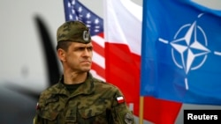 FILE - A Polish soldier stands in front of U.S., Polish and NATO flags ahead of military exercises in Swidwin, northwestern Poland.