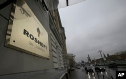 FILE - A plaque for the Rosneft Oli Company is seen outside the company headquarters in Moscow, Russia, Oct. 18, 2012.