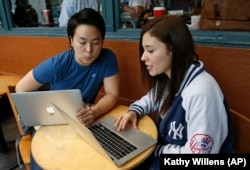 Colombian-born immigrant Nathaly Ordonez, right, studies her next semester's class options at the tuition-free, online University of the People, Thursday, Nov. 5, 2015, in New York, with Shota Hanawka, at left.