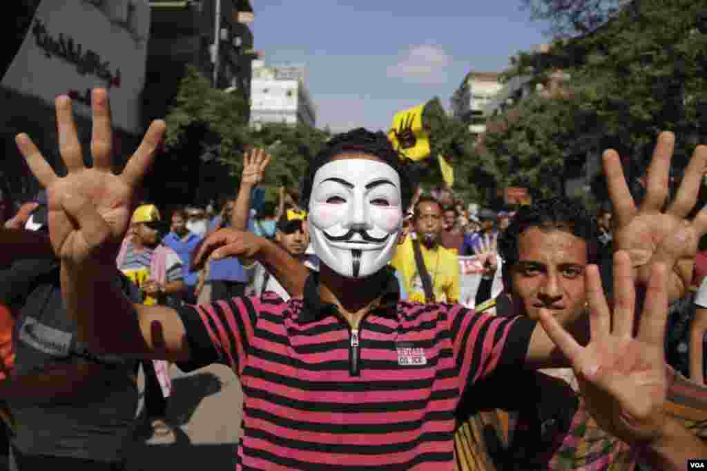 A masked protester holds up four fingers as he marches in Maadi, southern Cairo, Sept. 20, 2013. (Hamada Elrasam for VOA)