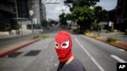 Một người biểu tình mang mặt nạ người nhện góp tay dựng chướng ngại vật trên đường phố trong cuộc đình công chống chính phủ ở Caracas, Venezuela hôm 20/7/2017.