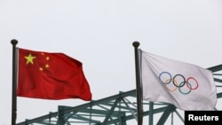 A Chinese national flag flutters next to an Olympic flag at the Beijing Organising Committee