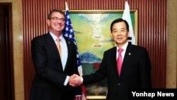 지난해 5월 싱가포르에서 열린 제14차 아시아안보회의(샹그릴라 대화)에 참석한 한민구 국방부 장관(오른쪽)과 애슈턴 카터 미국 국방장관이 미한 국방장관 회담에 앞서 악수하고 있다. (자료사진)